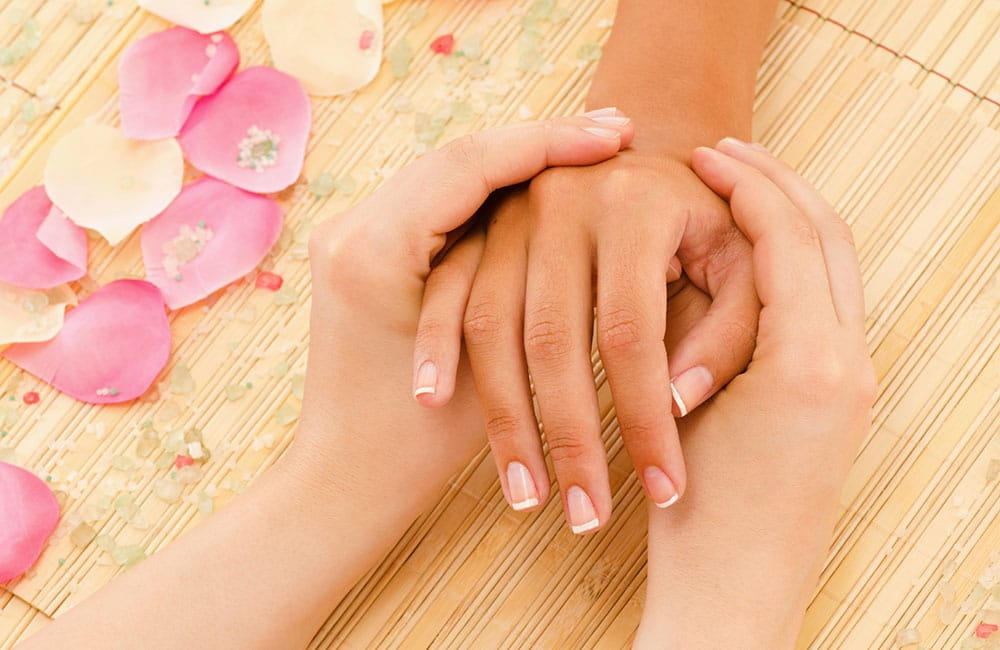 massage marketing tips: two hands giving another hand a reflexology massage