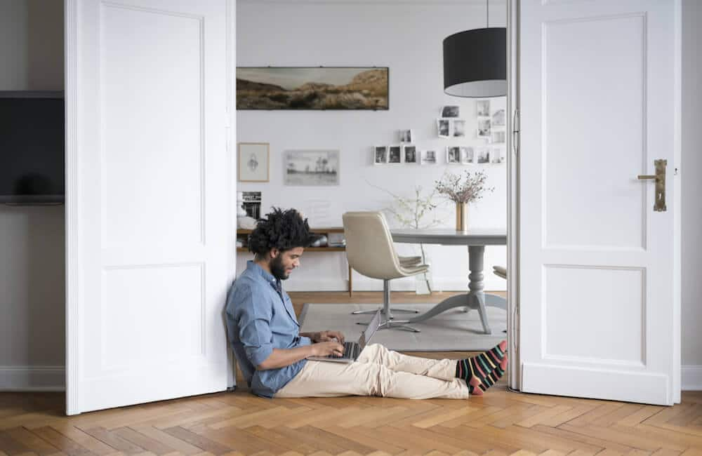 At home office Small Space Home Office Tax Deductions For Remote Workers Man Sitting On Floor At Home Working On Lovelace Interiors Home Office Tax Deductions For Remote Workers